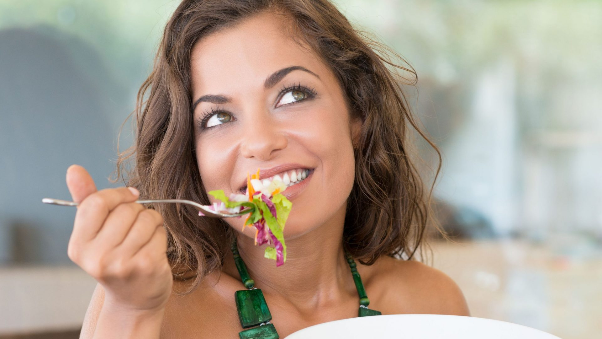 35534884 - portrait of young happy woman eating salad at cafeteria